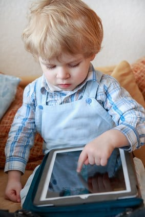 Little toddler boy of two years playing with tablet pc .