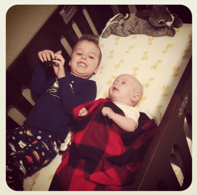 Big Brother with baby in his crib
