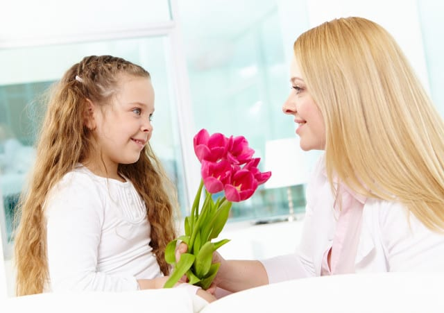 Adorable girl giving beautiful tulips to her mother